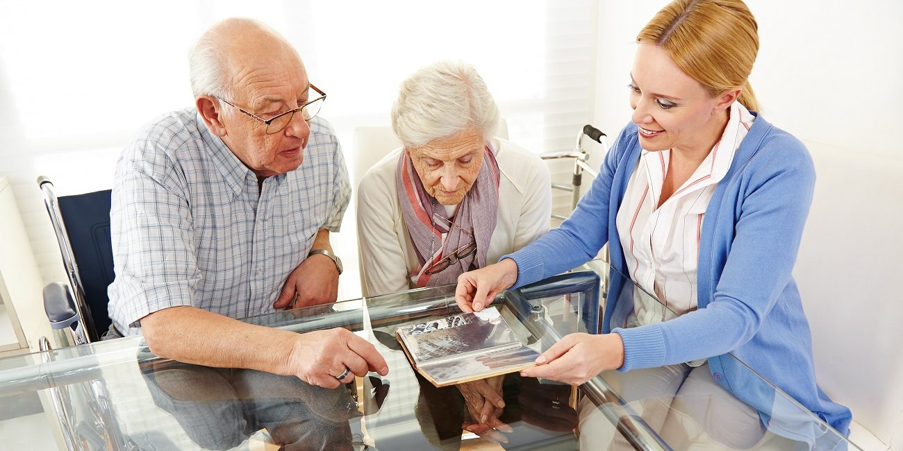 Senior citizens couple watching a photo album with their daughte